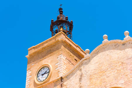 View of the church tower with clock in Sitges, Barcelona, Catalunya, Spain. Isolated on blue background Stock Photo