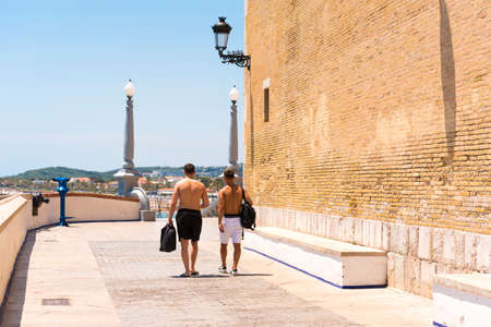 Two men go through the historic center in Sitges, Barcelona, Catalunya, Spain. Copy space for text