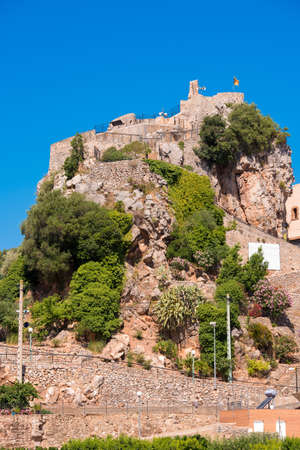 The mountain town of Pratdip in Spain. Copy space for text. Isolated on blue background. Vertical