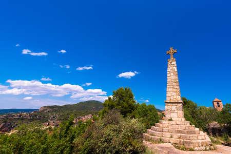 Memorial Cross and Church of Santa Maria de Siurana in Siurana de Prades, Tarragona, Catalunya, Spain. Copy space for text. Isolated on blue background