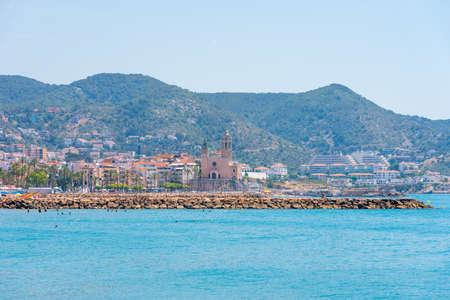 Stony beach and church of Sant Bartomeu and Santa Tecla in Sitges, Barcelona, Catalunya, Spain. Copy space for text