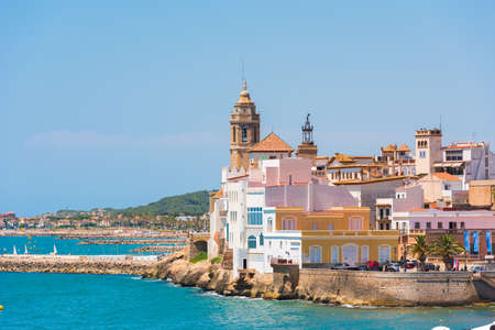 View of the historical center and the church of Sant Bartomeu and Santa Tecla in Sitges, Barcelona, ??Catalunya, Spain. Copy space for text. Isolated on blue background