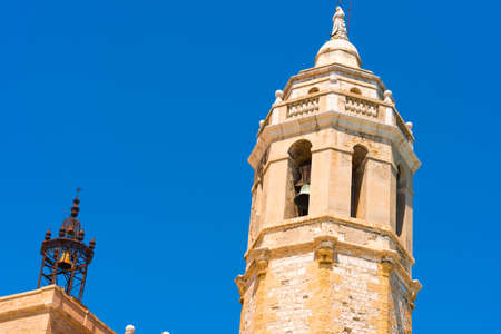 View of the tower of the church of Sant Bartomeu and Santa Tecla in Sitges, Barcelona, Catalunya, Spain. Copy space for text. Isolated on blue background