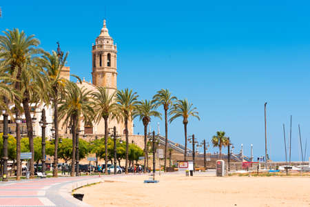 SITGES, CATALUNYA, SPAIN - JUNE 20, 2017: View of the embankment and �hurch of Sant Bartomeu and Santa Tecla. Copy space for text. Isolated on blue background Редакционное