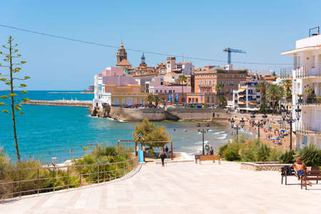 SITGES, CATALUNYA, SPAIN - JUNE 20, 2017: View of the historical center and the �hurch of Sant Bartomeu and Santa Tecla. Copy space for text. Isolated on blue background