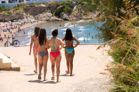 Four girls in bathing suits go to the beach in Sitges, Barcelona, Catalunya, Spain Stock Photo
