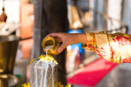 A ritual of Hindu religion. A solution of rice flour pours on the sculpture Lingam. Close-up Stock Photo