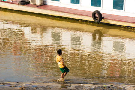 BAGAN, MIANMAR - DECEMBER 1, 2016: The boy on the bank of the Irrawaddy river, Burma. Copy space for text