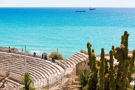 TARRAGONA,SPAIN  MAY 1, 2017: View of the ancient Roman amphitheater and the sea. Cactus in the foreground. Copy space for text Editorial