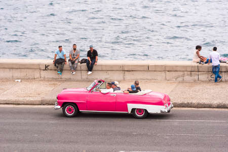CUBA, HAVANA - MAY 5, 2017: American pink retro cabriolet rides along the Malecon seafront. Copy space for text Editorial