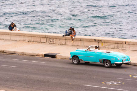 CUBA, HAVANA - MAY 5, 2017: American azure retro cabriolet rides along the Malecon seafront. Copy space for text