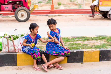 PUTTAPARTHI, ANDHRA PRADESH, INDIA - JULY 9, 2017: Two Indian girls on the street. Copy space for text