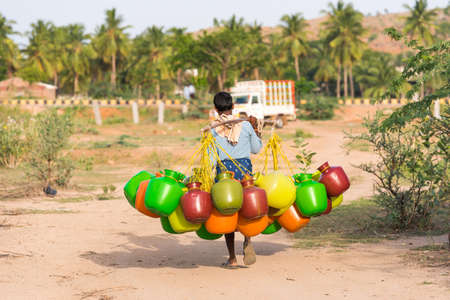 Indian man goes for water, Puttaparthi, Andhra Pradesh, India. Copy space for text Stock Photo