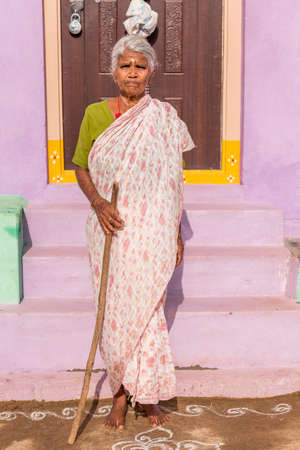 PUTTAPARTHI, ANDHRA PRADESH, INDIA - JULY 9, 2017: An elderly Indian woman at the doorstep of a house. Copy space for text. Vertical