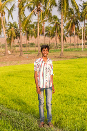 PUTTAPARTHI, ANDHRA PRADESH, INDIA - JULY 9, 2017: Portrait of an indian guy in a field. Copy space for text. Vertical
