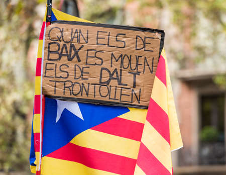 Poster against the background of the Catalan flag at the demonstration, Barcelona, ??Catalunya, Spain. On that banner is said: