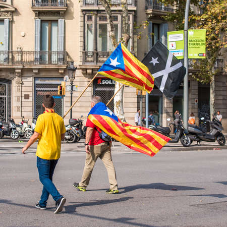 BARCELONA, SPAIN - OCTOBER 3, 2017: Demonstrators bearing catalan flag during protests for independence in Barcelona. Copy space for text Editorial