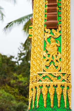 craftmanship: The bas-relief on the wall of the temple in Louangphabang, Laos. Close-up. Vertical