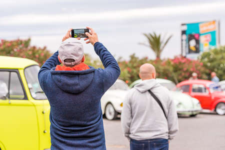 AGDE, FRANCE - SEPTEMBER 9, 2017: A man is taking pictures of cars. Copy space for text