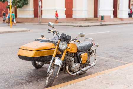 Yellow retro motorcycle on city street, Cuba, Havana. Copy space for text