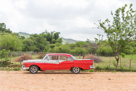 CUBA, HAVANA - MAY 5, 2017: American red retro car in the countryside. Copy space for text
