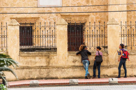 SANTO DOMINGO, DOMINICAN REPUBLIC - AUGUST 8, 2017: Three girls near a building on a city street. Copy space for text