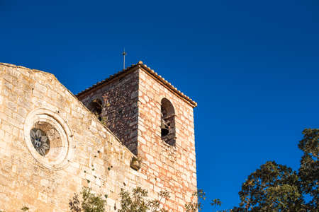 View of the Romanesque church of Santa Maria de Siurana, in Siurana, Tarragona, Spain. Copy space for text. Isolated on blue background