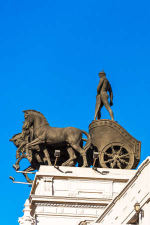 MADRID, SPAIN - SEPTEMBER 26, 2017: Sculpture of a chariot, over a bank building on the street Alcala. Copy space for text. Vertical