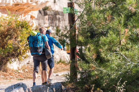 SIURANA DE PRADES, SPAIN - OCTOBER 5, 2017: Tourists with backpacks in the mountains. Copy space for text Editorial