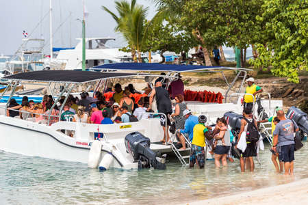 BAYAHIBE, DOMINICAN REPUBLIC - MAY 21, 2017: Tourists get into boat. Copy space for text