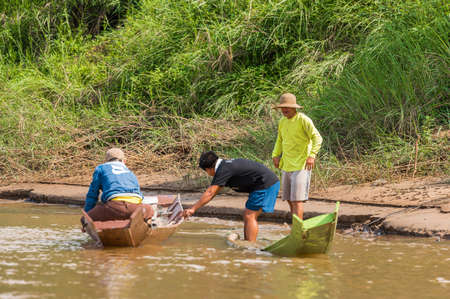 LOUANGPHABANG, LAOS - JANUARY 11, 2017: Three men with boats on the bank of the Nam Khan river. Copy space for text Stock Photo