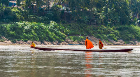 LOUANGPHABANG, LAOS - JANUARY 11, 2017: Monks in a boat on the river Nam Khan river. Copy space for text Editorial