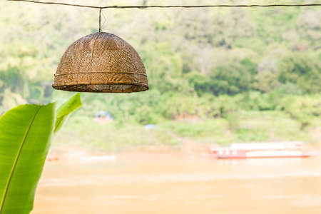 Wicker lamp in an outdoor cafe in Louangphabang, Laos. Copy space for text
