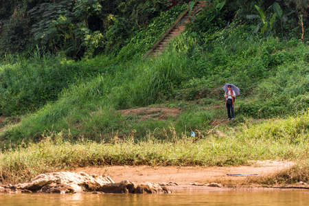 LOUANGPHABANG, LAOS - JANUARY 11, 2017: A man with an umbrella on the bank of the of the Nam Khan river. Copy space for text Editoriali