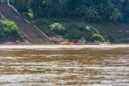 Monks in a boat on the river Nam Khan river, Louangphabang, Laos. Copy space for text