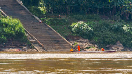 Monks in a boat on the river Nam Khan river, Louangphabang, Laos. Stock Photo