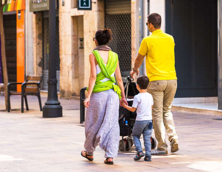 A married couple with a stroller on a city street, Tarragona, Catalunya, Spain. Copy space for text