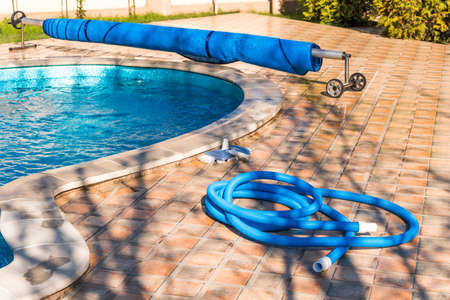 Manual equipment for cleaning pool, brush, hose, swimming pool cover, Yesulskaya, Krasnodar, Russia. Copy space for text