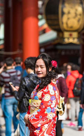 TOKYO, JAPAN - OCTOBER 31, 2017: Girl in a red kimono near the temple Senso-ji. Vertical