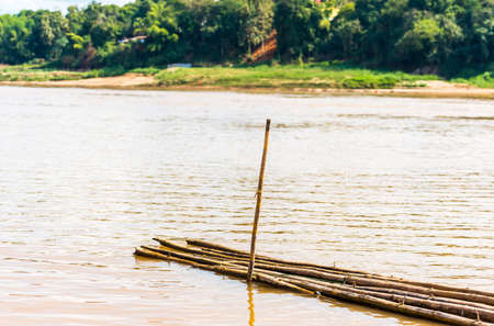 Bamboo sticks by the river Nam Khan in Luang Prabang, Laos. Copy space for text