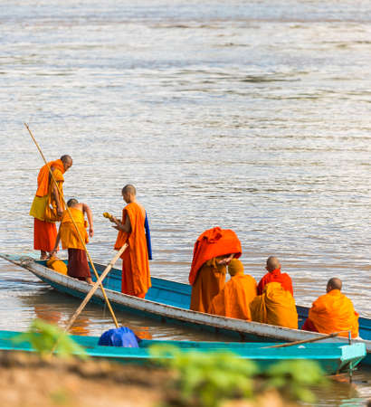LUANG PRABANG, LAOS - JANUARY 11, 2017: Monks in a boat on the river Nam Khan river. Copy space for text