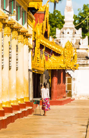 Woman near a buddhist temple in Bagan, Myanmar. Back view. Copy space for text. Vertical Stock Photo