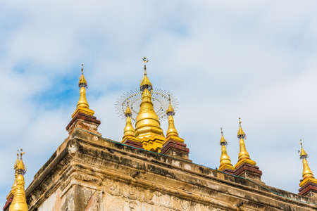 Pagodas with golden tips at the top of the Manuha temple in Bagan, Myanmar. Close-up