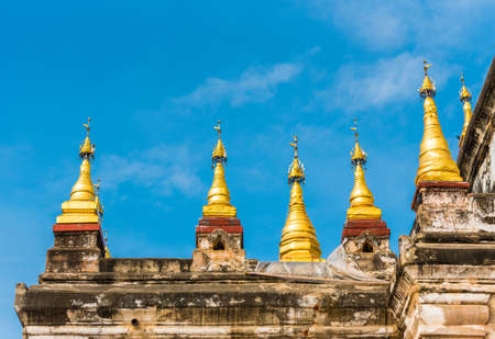 Pagodas with golden tips at the top of the Manuha temple in Bagan, Myanmar. Close-up. Isolated on blue background