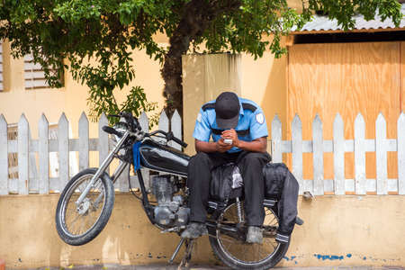 A policeman on a motorcycle on a city street, Santo Domingo, Dominican Republic. Copy space for text Imagens