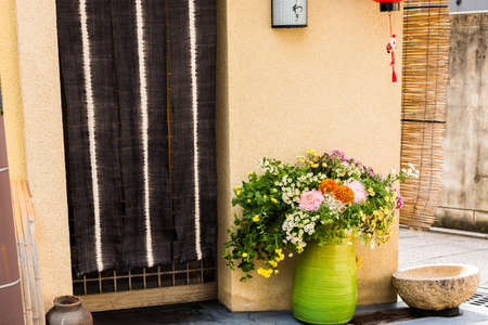 Green vase with wild flowers on a city street in Kyoto, Japan. Copy space for text