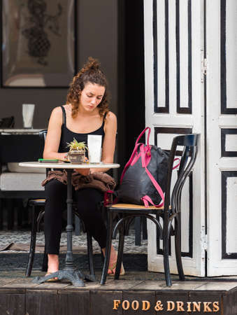 LUANG PRABANG, LAOS - JANUARY 11, 2017: Girl in outdoor cafe. Copy space for text Editorial