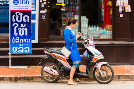 LUANG PRABANG, LAOS - JANUARY 11, 2017: Woman on a moped on a city street. Copy space for text