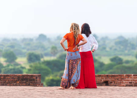 Two women in the background of a rural landscape in Bagan, Myanmar. Copy space for text
