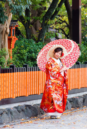 KYOTO, JAPAN - NOVEMBER 7, 2017: A girl in a kimono with an umbrella on a city street. Vertical. Copy space for text